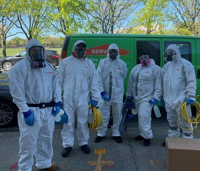 SERVPRO team members, donned in PPE, standing in front of SERVPRO van