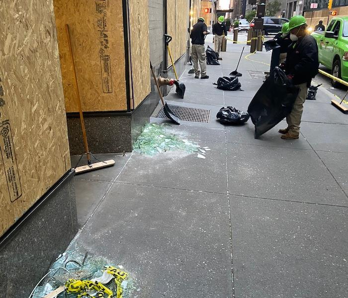 sidewalk with SERVPRO employees cleaning up glass