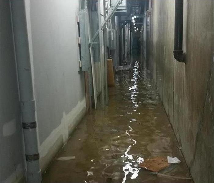 standing water in a narrow service corridor of a commercial building