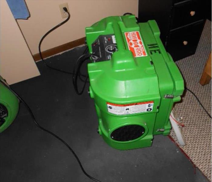 green air scrubber on a carpet with part of an air mover in the photo