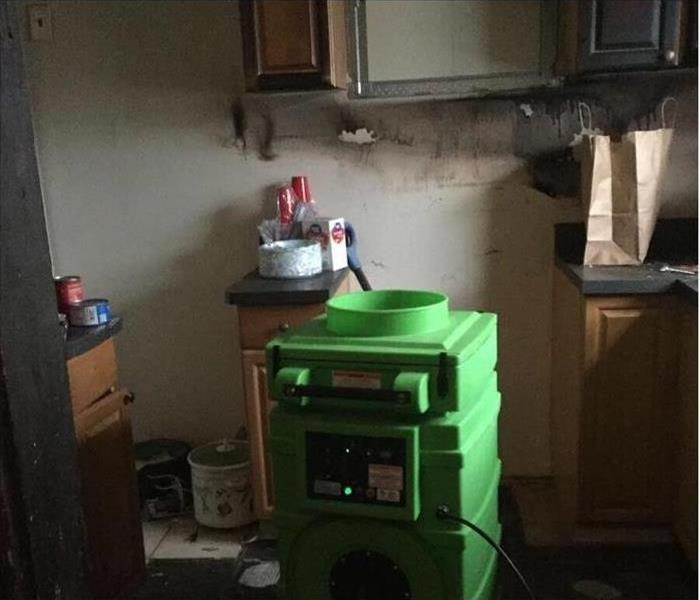 removed appliances from a burned kitchen with a green air scrubber working